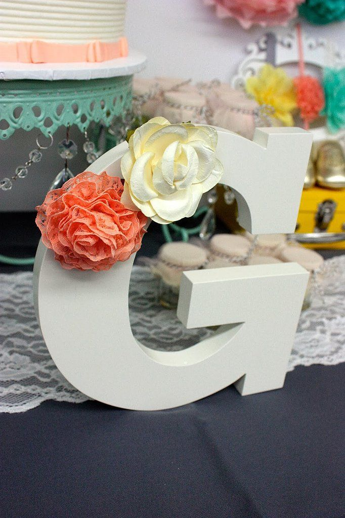 Making this DIY decoration was supersimple! Claudia purchased the wooden letter from Land of Nod ($5) and made the flowers out of fabric. After the party, the mom-to-be added the letter to Georgia's nursery.   Source: Tini Post