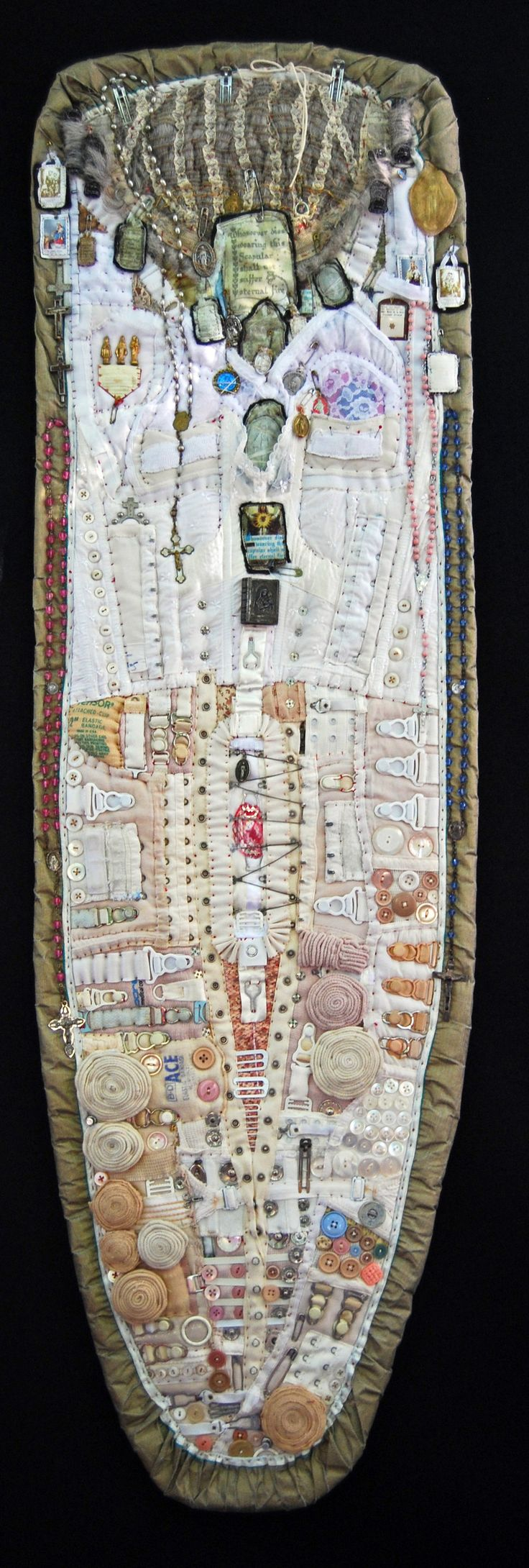 """Diane Savona - Reliquary, 52""""h x 15""""w - ironing board with her mom's collection of scapulars: Framed on an old ironing board cover, this holds her bras and girdles, her (rolled up) Ace bandages and her buttons, the strips of snaps and hooks, the girdle clips and pins. And of course her rosaries. She would be utterly appalled to know that people were seeing this."""