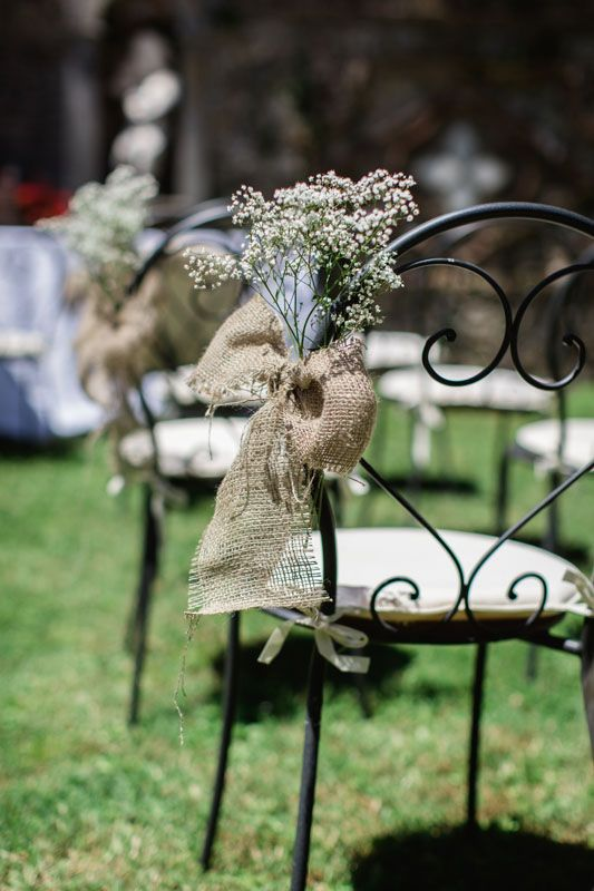 Wedding Isle Flower Ideas - Hessian bows with gyp (gypsophila) - Outdoor Wedding in Italy -  Alternative to chair covers - Country Style Wedding http://www.hardysflowers.co.uk/