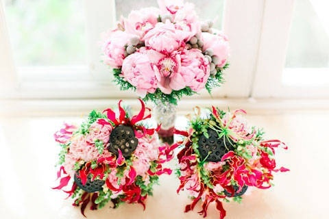 The bridesmaids' hand-tied bouquets of pink lisianthus, snapdragons, gloriosa lilies, and dried lotus ponds complemented the bride's bouquet.