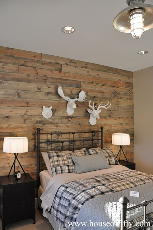 source: House of Fifty  Rustic cabin style bedroom with reclaimed wood planked wall featuring a trio of faux taxidermy wildlife over iron bed dressed with gray sheets layered alongside gray and black plaid bedding and a gray coverlet with matching pillow sham. A pair of black nightstands flank the bed topped with black tripod table lamps below a gray ceiling adorned with a galvanized metal barn light pendant.