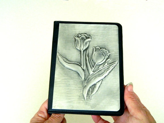 A Kindle cover with a beautiful tulip design in pewter repousse designed to fit various Kindle models: Kindle 3+3G, Kindle 4+4G, Kindle Touch, Kindle Fire.     Should you have a different Kindle, I'll source the cover for you and fit the pewter design to it.  If you already have a Kindle, give me the measurements and I'll make a pewter design for it and you can attach it yourself.