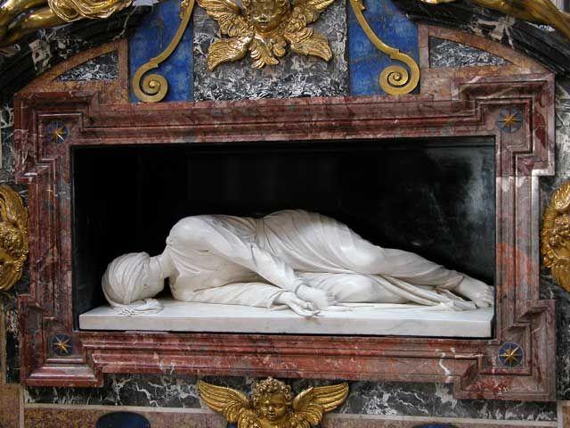 Basilica di Santa Cecilia : statua di Santa Cecilia , capolavoro di Stefano Maderno , in marmo bianco che riproduce fedelmente la posizione del corpo in cui fu trovata la Santa Martire durante gli scavi di restauro della chiesa di Santa Cecilia nel 1599 . [da VISITARE]