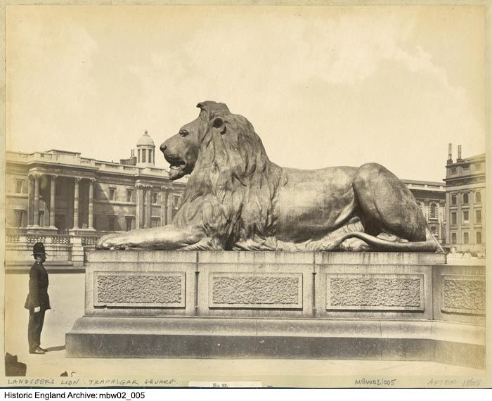 MBW02/005 A uniformed policeman stood beside one of the bronze lions at the base of Nelson's Column in Trafalgar Square.  Please click on the image for more information or to search or collections further.