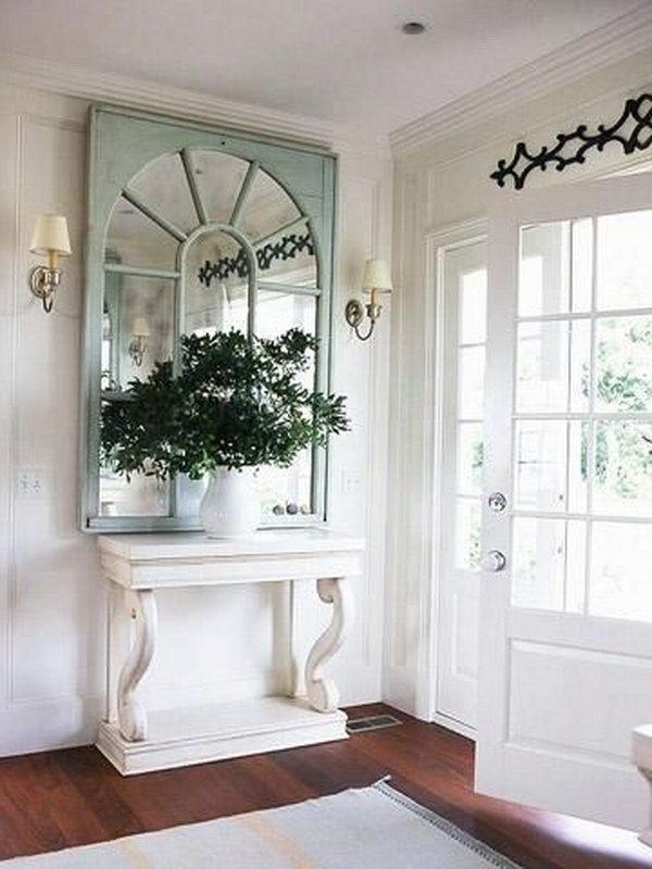 Vintage and chic. The white-painted vintage console with an old window framed mirror, fresh greens...add vintage yet chic charm to the decor.