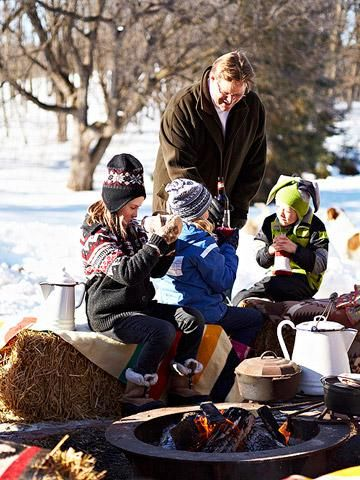A bonfire provides the focal point for a snow-day party. Blanket-topped hay bales surround the flames and provide easy seats. Recycled-sweater koozies protect fingers from cold drinks.