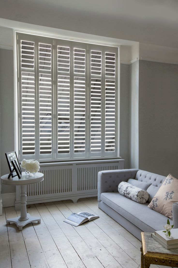 Reflect the light back into your living room with Luxaflex® Mirror Shutters. This full window looks stunning with silver mirror shutters giving a contemporary look to a minimal interior. #Luxaflex #InteriorShutters #MirroredInteriors #HomeStyle