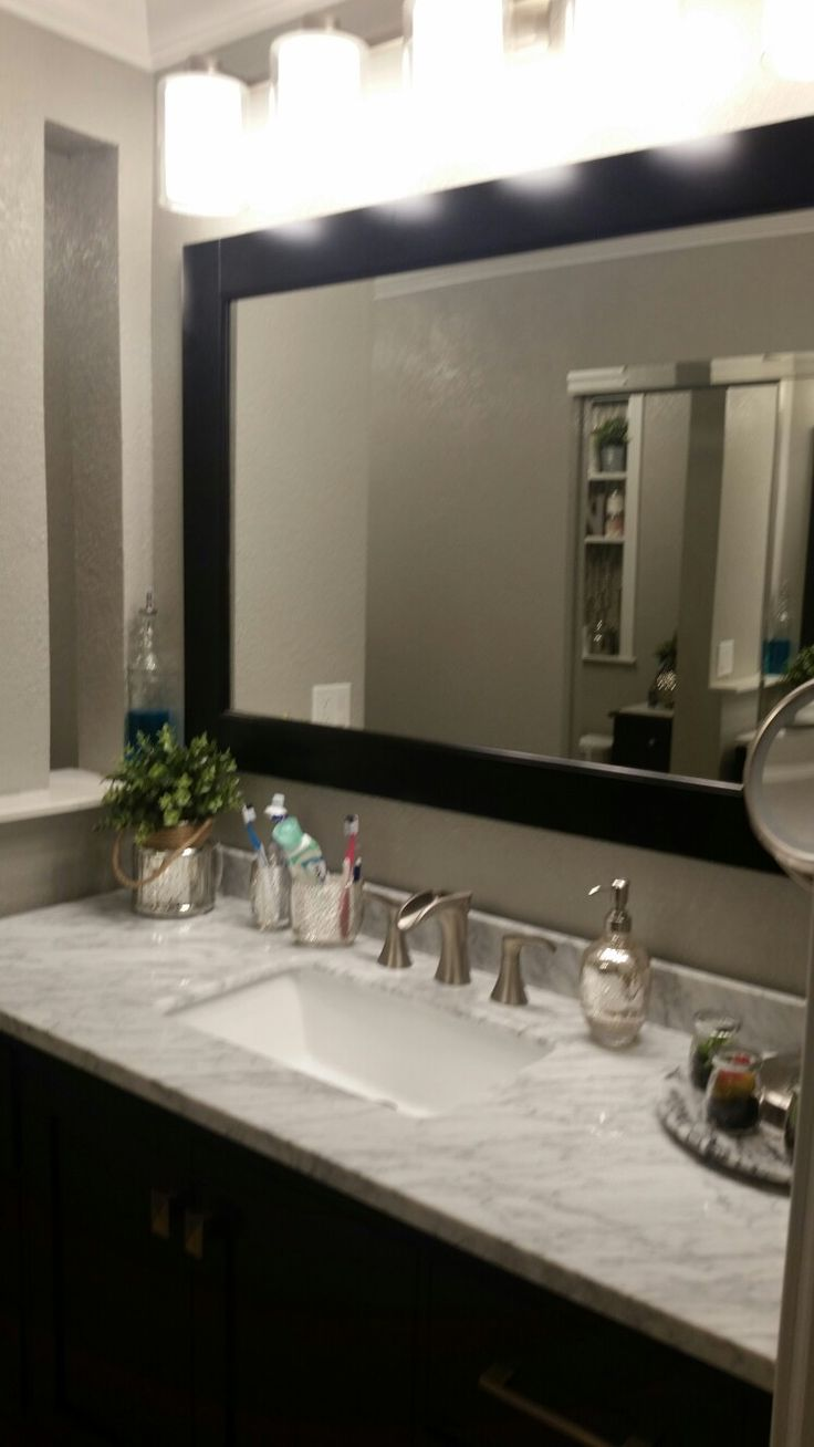 Espresso transitional bathroom vanity with carrara marble top decorated with silver mercury glass bathroom accessories and some small cactuses and Ikea plants. The bathroom is painted Gray and the color is Mindful Gray from Sherwin-Williams. I've added a built-in niche, thin, window panel to let light in.