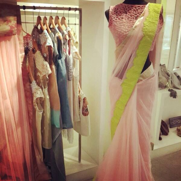 Baby pink saree with lime green border and sleeveless high neck blouse. Archana Rao.