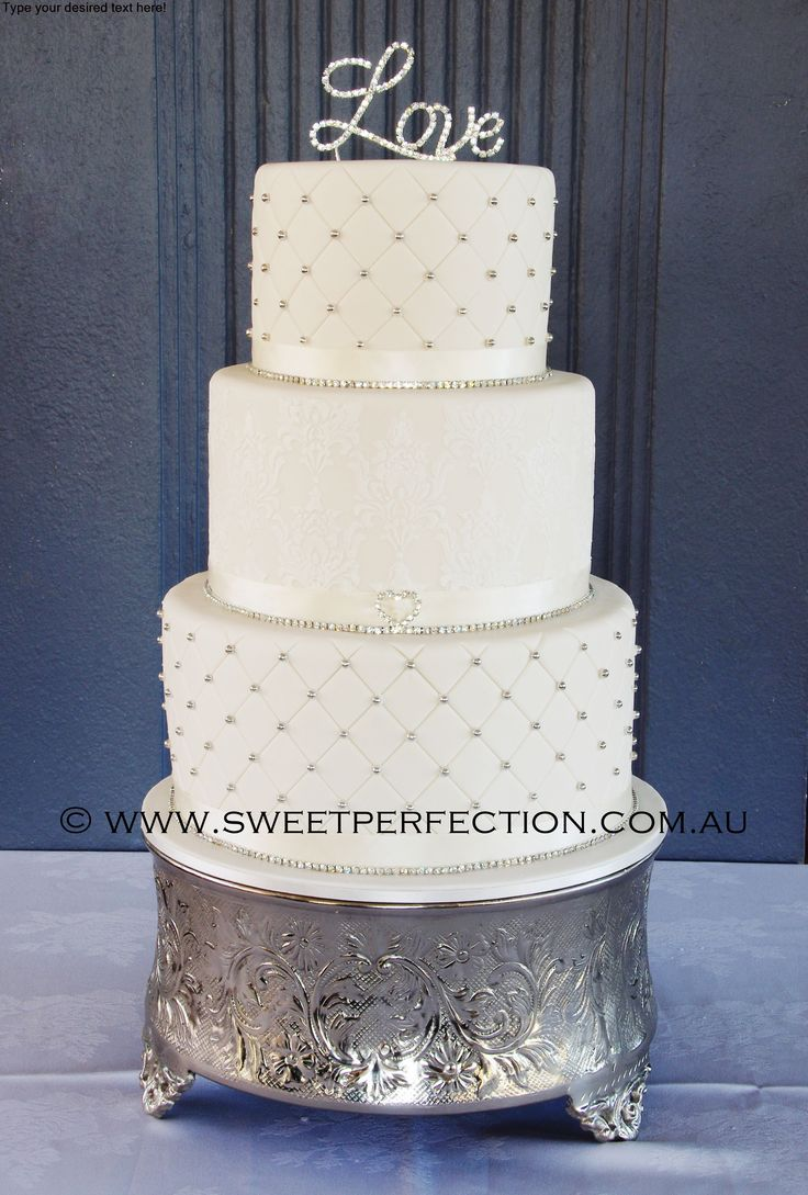 Three tiered ivory wedding cake, with quilting/cachous ...