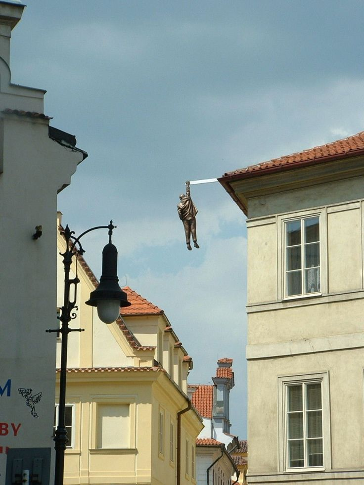 Man hanging out sculpture by David Cerny in Husova street in the Old Town