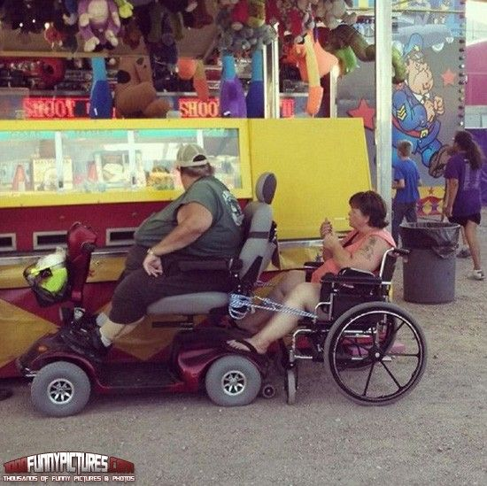 Fat man in motorized scooter tows woman in wheelchair at for Motorized cart for seniors