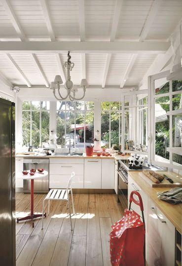 Une cuisine lumineuse installée dans la véranda de cette maison de pêcheur - Joyeuse maison au Cap Ferret - CôtéMaison.fr