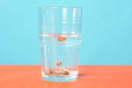 Experimente für Kinder: In diesem Versuch bringen Sie Rosinen in einem Wasserglas zum Tanzen. Rosinen haben eine größere Dichte als das Wasser und sinken deshalb zu Boden. Dort heften sich kleine Bläschen aus dem Sprudelwasser an die raue Oberfläche der Trockenfrüchte. Das Gas in den Bläschen – Kohlenstoffdioxid (CO2) – ist  viel leichter als Wasser. Wenn sich genug Bläschen an ihre Oberfläche geheftet haben, heben sie die Rosine hoch.