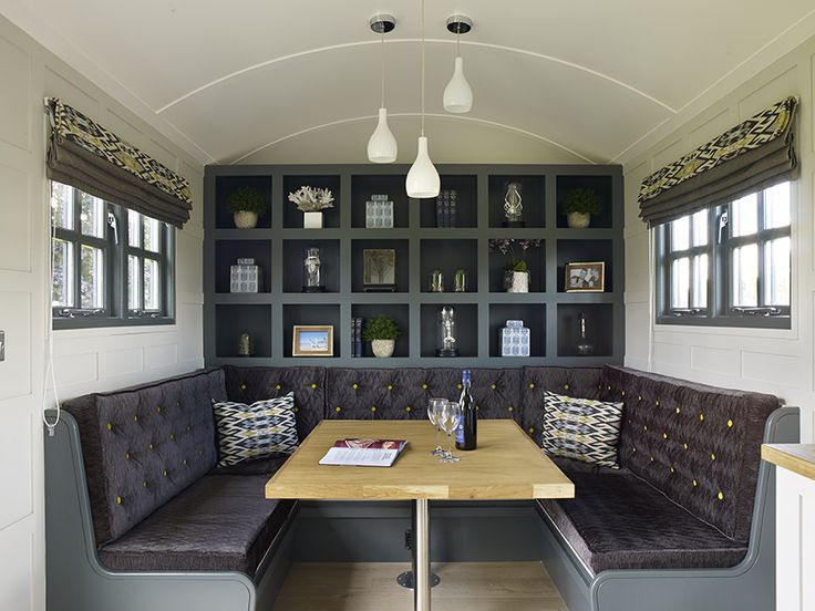 The interior of the Chatsworth Shepherd Hut with panelled walls, banquette seating and feature storage.