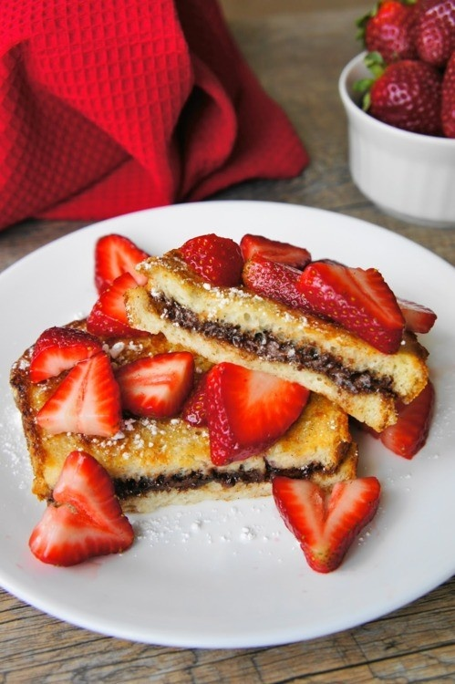 Nutella-stuffed French Toast! Made this, only I put the strawberry slices inside the sandwich before battering and cooking and it was amazing! I think next time I'll use regular bread though, instead of the super thick Texas toast! Still, it was awesome!!!!!!  ~ Nat
