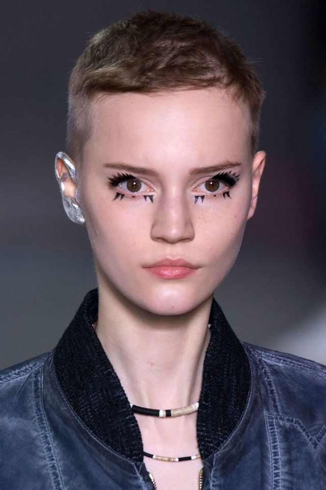 "Pat McGrath continued her love affair with all things metallic for spring, juxtaposing doll-like ""deconstructed lashes"" with a robotic silver ear.    - ELLE.com"