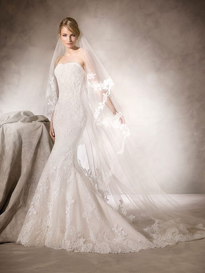 La Sposa HELGA This mermaid dress in Tulle and embroidered Tulle is decorated with guipure Lace embroidery and Gemstone applique. A strapless neckline embraces and flatters the figure.