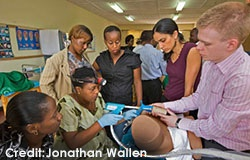 Einstein student Lukas Austin-Page assists during a PAP smear training in Rwanda while Lisa Nathan, M.D. (burgundy top) observes.