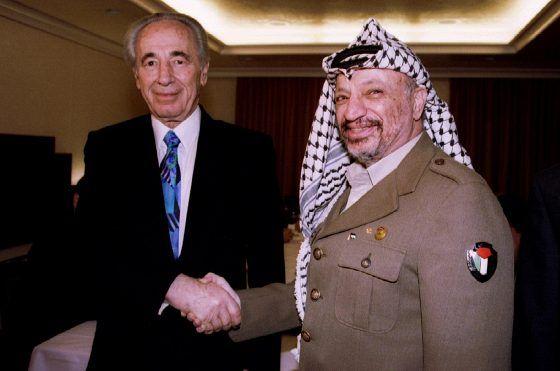 Ulkoministeri Shimon Peres ja Plo:n johtaja Jasser Arafat (oik.) kättelivät ennen neuvotteluita Sveitsin Davosissa 1994.