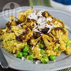Bloemkoolroosjes worden gemengd in een kruidige specerijenmengsel, in de oven gebakken en geserveerd in een kom met quinoa en erwtjes in een romige saus van kokosmelk.