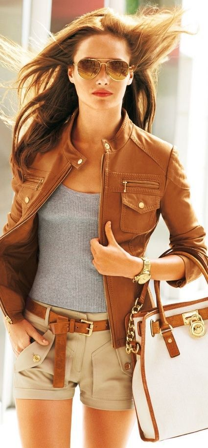 Brown leather jacket, grey top, and elegant shorts.