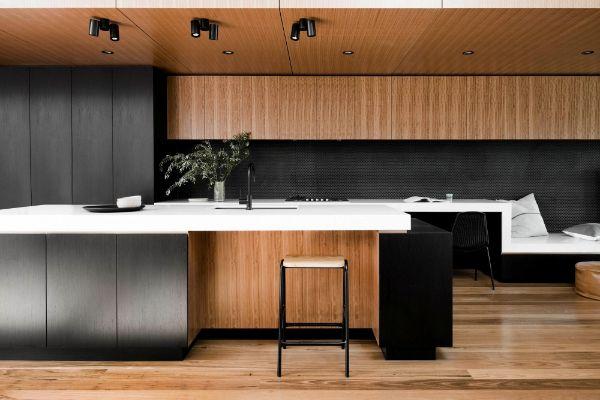 Blackbutt timber veneer contrasts a dark-stained Eveneer Raven veneer and white benchtops in the kitchen.