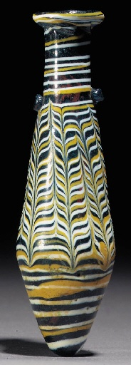 A HELLENISTIC CORE-FORMED GLASS ALABASTRON  2ND-1ST CENTURY B.C., EASTERN MEDITERRANEAN  The dark blue piriform body wound with opaque yellow and white marvered trail, combed into a feather design around the body, further spiral trail below, with applied twin vestigial handles on the shoulder  5¼ in. (13.3 cm.) high