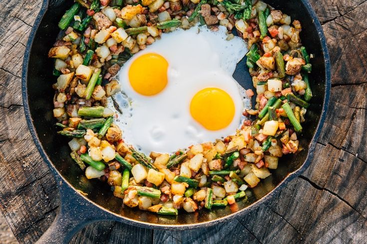 A hash of colorful asparagus, hearty potatoes, and savory pancetta topped with eggs form this delicious one pot camping breakfast skillet.