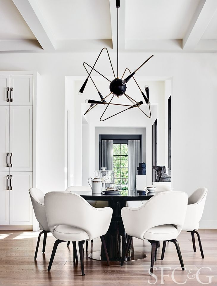In the breakfast area, a custom Orbital chandelier through Rewire is suspended above a Holly Hunt table and Hive Modern chairs.
