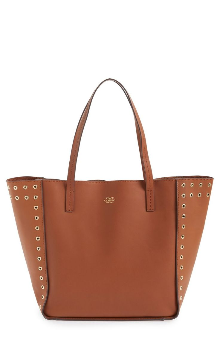 New favorite! Eye-catching rivets outline the side panels of this sleek leather tote from Vince Camuto in a streamlined, minimalist silhouette.