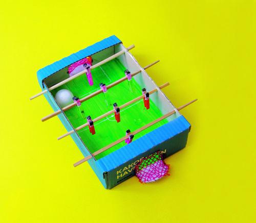 Il calcio balilla: serve 1 cassettina di cartone, 4 bacchette per cibo cinesi, 8 mollette di legno, 1 retina tipo quella delle arance, taglierino, pinzatrice, foratrice, colori e 1 pallina