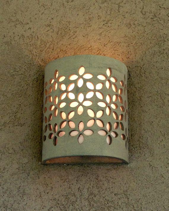 מנורת קיר מקרמיקה בעבודת יד, בגוון אפור טבעי (ללא גלזורה). מידות רוחב 18 ס''מ, גובה 22 ס''מ, עומק 8 ס''מ. האור מתפזר כלפי מעלה ומטה וכן דרך העלים שבדוגמה. ניתן להזמין בצבעים ובכמויות שונות. כרגע קיים במלאי רק בצבע שמנת.