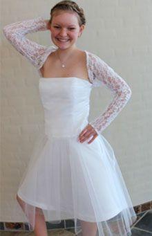 """Jeg har selv designet og syet denne kjole, da jeg gerne ville have både snøreryg og corsage med  tyl drapering. Ideen til skørtet er taget fra mønstret """"Melanie"""", og boleroen er syet efter mønsteret  """"Nicole"""". Kjolen er syet i brudesatin med brudetyl. Boleroen er syet i blondestof.  Til kjolen har jeg valgt at sætte et par hvide læder Converse, så der både var det fine i kjolen og det seje i skoene."""