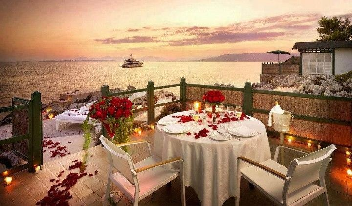 Romantic Dinner set with rose petals and candlelight... and the beautiful view of the ocean.  Yes, please!