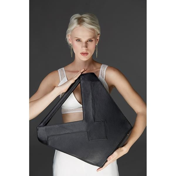 Whether you are going to a gallery opening, to the theatre, or simply meeting friends for coffee this super sleek structured tote is sure to impress.  Handmade in the U.S. out of high quality leather.  The inside is fully lined and includes a zip pocket and two flat wall pockets.  Comes with removable shoulder strap.