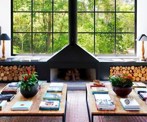 Twin coffee tables and stacks of books make the large living area of this Brazilian mountain retreat feel cozy. (Can I live here?)