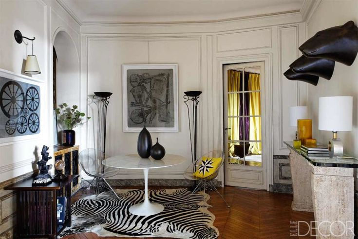 This Paris apartment is an eclectic mix of treasures.  My eye immediately goes to the two Art Deco inspired torchiere floor lamps that frame the room.  A 1930s console table echoes their origins. // 11 Art Deco Inspirations on MotleyDecor.com