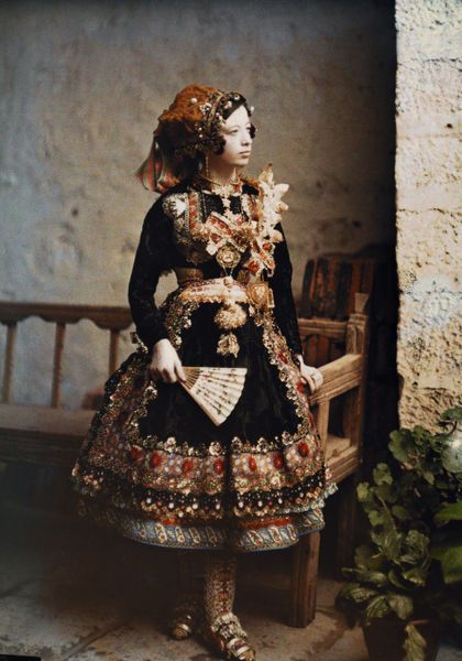 A girl poses in her traditional costume for an informal portrait."