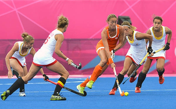 Maartje Paumen of Netherlands dribbles past defenders of Belgium during the preliminary round women's field hockey match