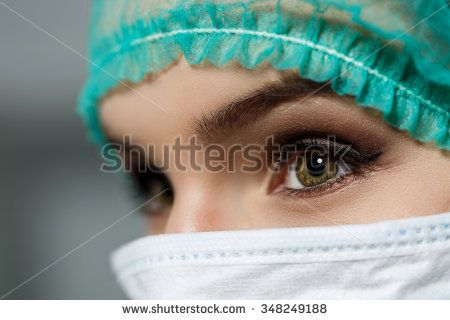 Female doctor face wearing protective mask and green surgeon cap closeup. Nurse eyes close up gazing intently. Resuscitation, emergency, save patient life, surgery, medical help and insurance concept