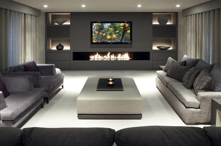 Elegante living moderno con grande camino, tv e particolare illuminazione della parete centrale