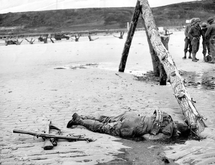 """https://flic.kr/p/fwN4MR   p012584   N° 26-G-2397 Omaha Beach, après le D-Day. Sur l'estran  pied d'un obstacle de plage dénommé Hemmbalken git le corps d'un GI qui n'a pas encore été ramassé, en arrière-plan un groupe de GI's indifférents. Ces obstacles étaient souvent minés avec des Tellerminen antichar, mais l'alternance des marées a empêché beaucoup d'entre elles de fonctionner.  www.flickr.com/photos/mlq/9529864082/in/photostream/ A côté deux fusils : M1-Garand et M 1903 """" Springfi..."""