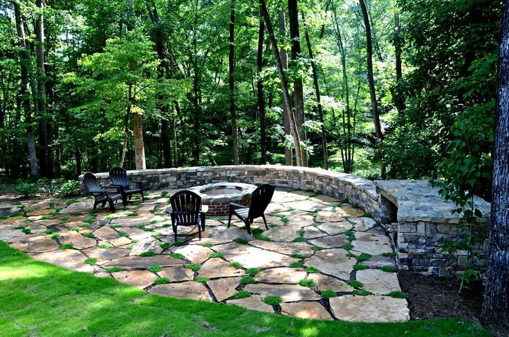 A quiet place to relax 'away from it all'. Custom fire pit with flagstone patio. We installed a large retaining wall to transform an inaccessible backyard slope into a private outdoor space nestled on the edge of a wooded backdrop.