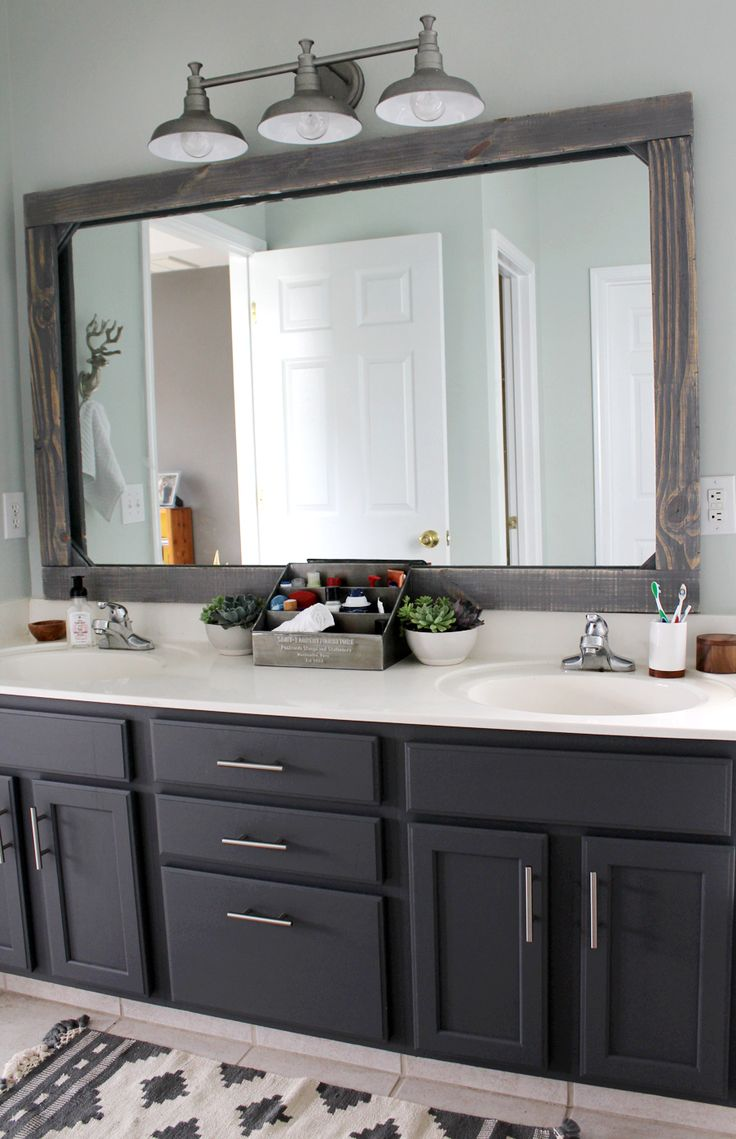 "Just a few weeks ago we finished our master bathroom makeover on a tiny budget (about $300!) and I received several requests for a tutorial on how to make the mirror. Full disclosure--covering our mirror wasn't my original idea! I spotted it at Cherished Bliss several months ago and I was determined to try it for ourselves! Our frame size ended up being 66"" x 42."" I give dimensions as a guideline below, but PLEASE measure your own mirror and adjust your measurements accordingly! The wood"