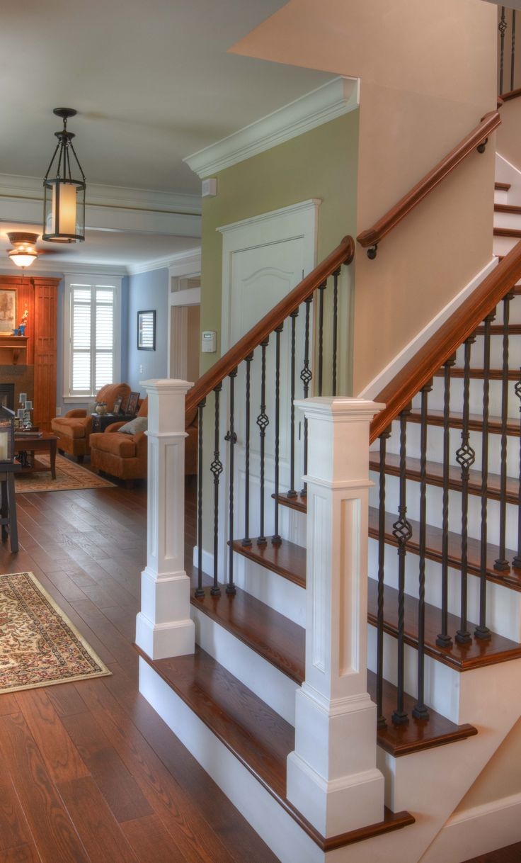Hardwood flooring up the stairs = classic look. Rod Iron balusters, wood  railings,