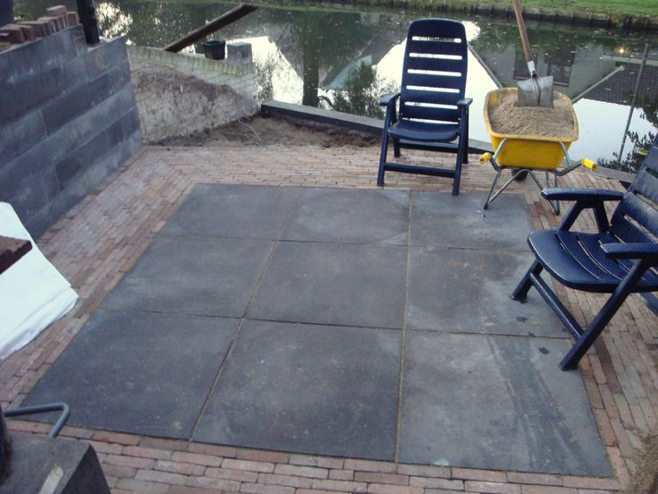 Hier is het terras gemaakt, laag bij het water. De bestrating is gelegd met gebakken klinkers met in het midden oud-hollandse tegels.