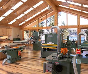 A Well Lit Large Wood Shop. Wood Shop: Lots Of Big Green Machines, Lighting  In Ceiling, Dust Collection Below