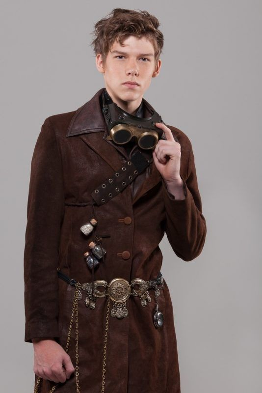 The jewelry adorned with gears and mechanical dials, brass goggles, and what looks like a pocket watch chain dangling from his waist really bring out the Steampunk vibe in this look. Add all of that to a great look leather coat and you've got yourself an awesome looking Steampunk look for guys!