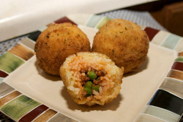 Sicilian rice balls, stuffed with meat sauce, breaded, and fried until golden. To most tourists, this is street food. You don't really get arancini in restaurants. But to Sicilians, an aranci…